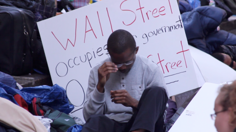 A tired protestor rests up against his sign.